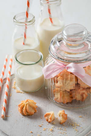 Shortbread cookies in glass jar served with milk and straw on white table