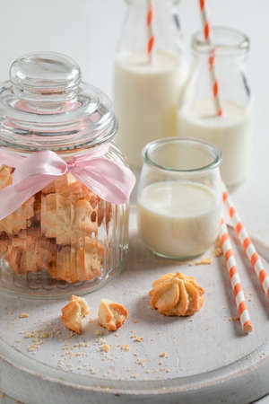 Sweet butter cookies served with milk and straw on white table Stok Fotoğraf