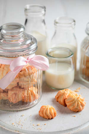 Sweet butter cookies in a large glass jar on white table
