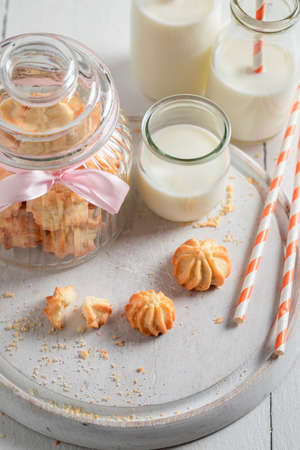 Delicious butter cookies served with milk and straw on white table
