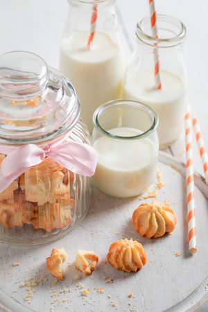 Homemade butter cookies served with milk and straw on white table