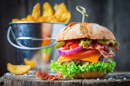 Delicious sandwich made of beef, vegetables and cheese. American cuisine.