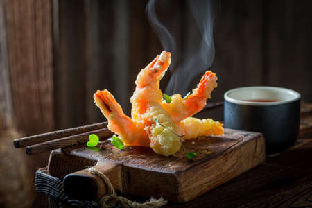 Tasty shrimp in tempura with red sauce on black background. Old Chinese cuisine.