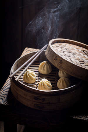 Boiled and hot manti dumplings in wooden steamer. Old Chinese cuisine.