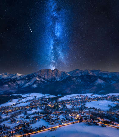Milky way over illuminated Zakopane city in winter. Night hiking in the mountains