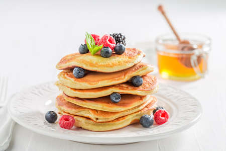 Sweet and homemade american pancakes with berries and honey. Pancakes for breakfast.