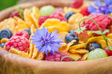 Flowers and fruits with cornflakes. Healthy and slimming breakfast in garden.