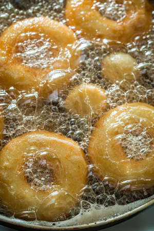 Closeup of frying tasty and homemade donuts on fresh oil. Homemade pastries. Donuts for Fat Thursday.