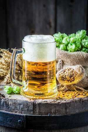 Pint of beer with foam. Brewing industry. Light beer on a wooden barrel