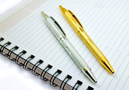 A set of gold and silver pen on a planner