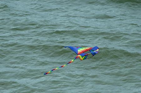 Kite flying over ocean Stock Photo
