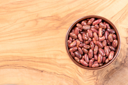 Pinto beans in a cup on olive wooden deck top view Archivio Fotografico