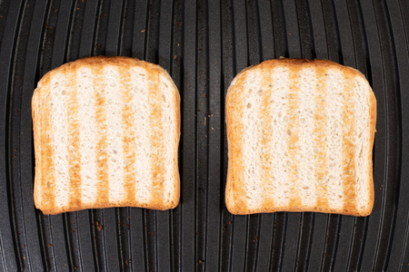 Toasted bread on the electric grill. Grilled bread with strips