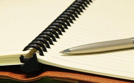 オフィスのテーブルでノートブックとボールのペン