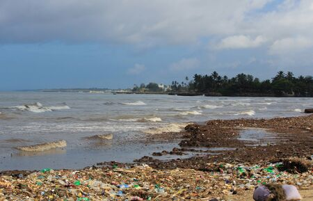 Sea Pollution: Garbage dumped in the Sri Lankan Sea near Colombo. women collects plastic things in a pile of garbage brought by the surf from the sea
