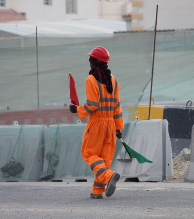 Road Construction Signal Man Helping Heavy vehicle on the road with red and green flag.