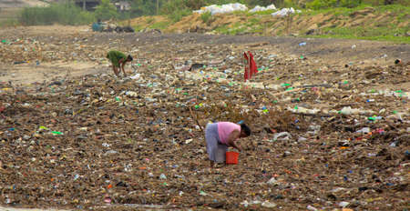 Sea Pollution: women collects plastic things in a pile of garbage brought by the surf from the sea in Sri Lanka beach.