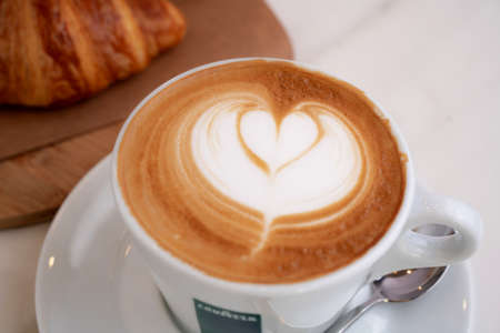 Background image of cappuccino in lavazza cup with croissant on the side
