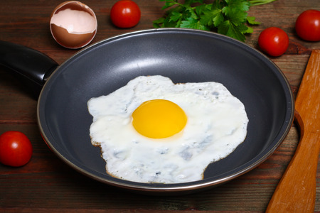 eggs and bacon: Pan of fried eggs, with cherry-tomatoes and parsley on a wooden table surface Stock Photo