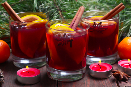 wood stick: Christmas mulled wine in glasses with orange on wooden table, close up Stock Photo