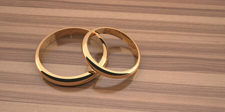Two golden wedding rings are large below and small above on a wooden table background
