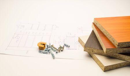 Möbeldetails und -elemente liegen auf einem weißen Blatt mit Produktzeichnungen.