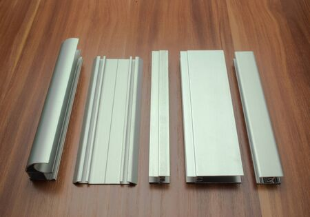 Aluminum profile for a sliding wardrobe is laid out on a wooden surface Stok Fotoğraf