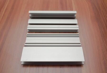 Aluminum profile for a sliding wardrobe is laid out on a wooden surface 免版税图像