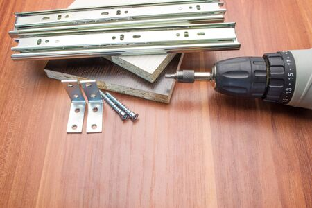Furniture details and electric framing against a mahogany background everything for assembly Stok Fotoğraf