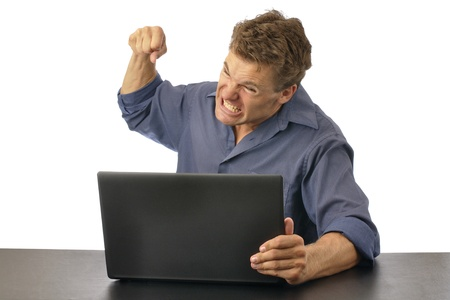 angry person: Angry man punching computer isolated on white background