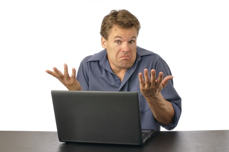 Puzzled man at computer shrugs shoulders and expresses lack of knowledge