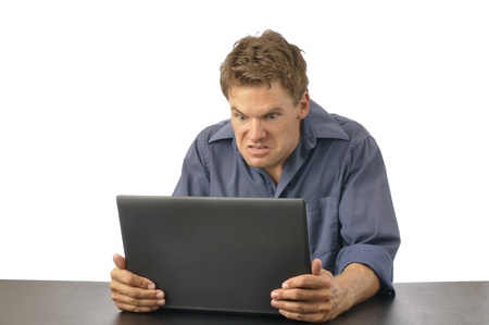 Angry man strangles laptop computer on white background photo