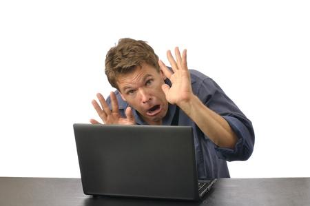 Angstige man met handen omhoog hurkt achter de computer Stockfoto