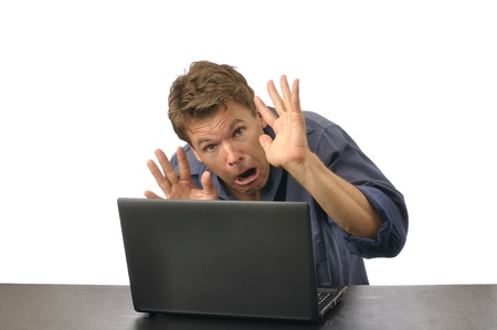 crouches: Fearful man with hands up crouches down behind computer