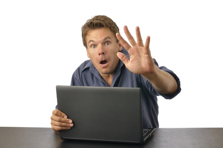 Man caught by surprise on computer raises hand to block view photo