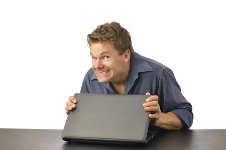embarrassed: Man with guilty grin carefully closes laptop Stock Photo