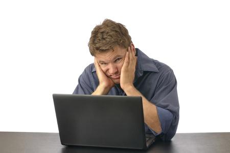 Man met blik van walging zit op de computer met het gezicht in handen