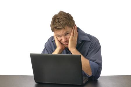 Man with look of disgust sits at computer with face in hands