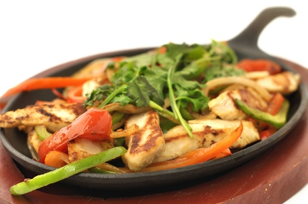 Hot skillet of grilled chicken fajitas with vegetables on white background