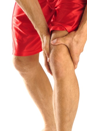 leg injury: Injured athlete in pain clutches his knee Stock Photo