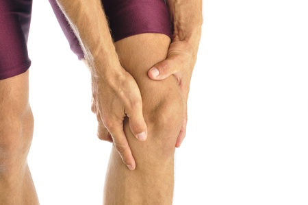 leg injury: Male athlete in pain clutches his knee Stock Photo