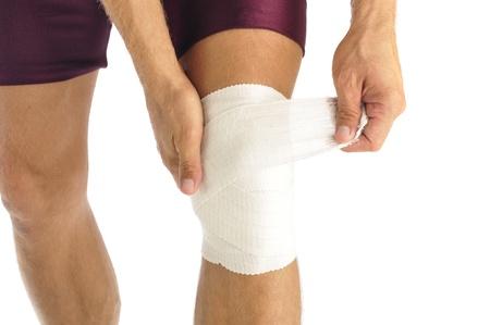 Male athlete wraps knee injury with bandage photo