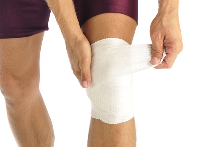 aching muscles: Male athlete wraps knee injury with bandage