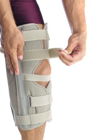 de rodillas: Atleta masculino ajusta su pierna con firme apoyo