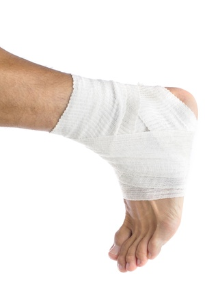 Ankle of male athlete wrapped in white bandages photo