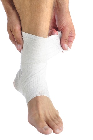 white bandage: Ankle of male athlete being wrapped with white bandage