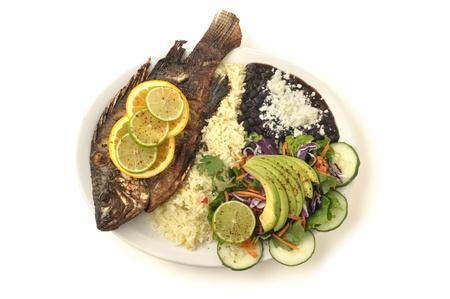 Plaat van gebakken hele tilapia met rijst, zwarte bonen en salade op een witte achtergrond