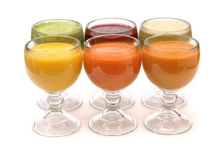 Six glasses of colorful fruit juices on white background photo