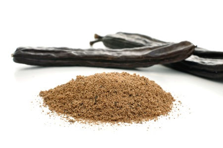 carob: Ground carob and carob pods on white Stock Photo