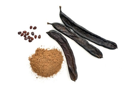 Carob pods, carob powder, and carob seeds on white background